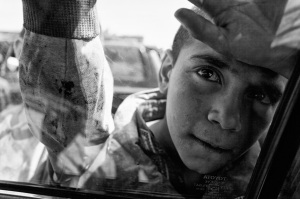 An Afghan child looking into a car