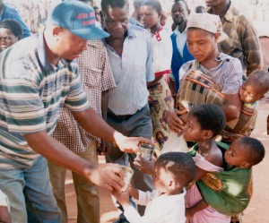 Peter distributing food to two refugee children.
