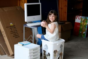"My youngest playing ""office"" on a broken iMac consigned to the garage."